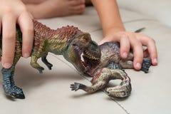 Jong geitje het spelen met speelgoed van tyrannosaurus en dinosaurus bloedig lichaam op bank royalty-vrije stock afbeelding