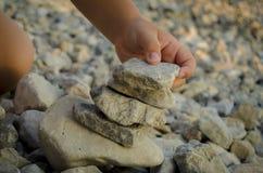 Jong geitje het spelen met stenen Stock Afbeeldingen