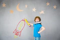 Jong geitje het spelen met straalpak thuis Stock Afbeelding