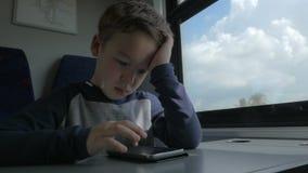 Jong geitje het spelen op cel wanneer het reizen door trein stock videobeelden