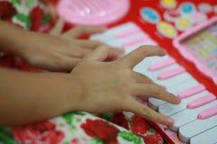 Jong geitje het spelen pianostuk speelgoed Stock Foto's