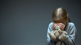 Jong geitje het verbergen achter teddybeer, kinderachtige fobie en vrees, het slachtoffer van het familiegeweld royalty-vrije stock foto
