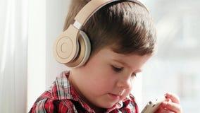 Jong geitje in hoofdtelefoons die aan muziek, jongen luisteren die de geruite beeldverhalen van het overhemdshorloge op smartphon stock videobeelden