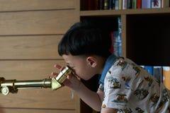 Jong geitje of jongensgebruikstelescoop stock afbeeldingen