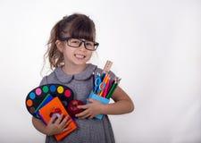 Jong geitje klaar voor school Leuk slim kind die in oogglazen schoollevering houden: pennen, notitieboekjes, schaar en appel royalty-vrije stock fotografie