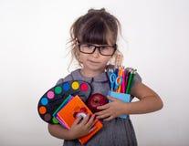 Jong geitje klaar voor school Leuk slim kind die in oogglazen schoollevering houden: pennen, notitieboekjes, schaar en appel royalty-vrije stock foto
