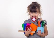 Jong geitje klaar voor school Leuk slim kind die in oogglazen schoollevering houden: pennen, notitieboekjes, schaar, wekker en ap royalty-vrije stock foto's