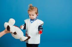 Jong geitje in medische eenvormig met stethoscoop, spuit op blauwe achtergrond stock fotografie