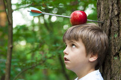 Jong geitje met appel op hoofd Stock Foto's
