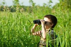 Jong geitje met binoculair Stock Afbeeldingen