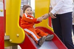 Jong geitje met een glimlach op glijbaan Stock Foto