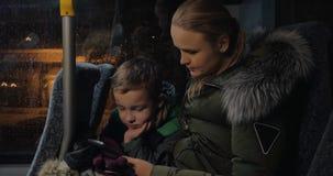 Jong geitje met moeder die cellphone in de bus gebruiken stock videobeelden