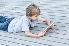 Jong geitje met tabletcomputer die op houten terras liggen Royalty-vrije Stock Afbeelding