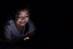 Jong geitje met tabletzitting op bed en het letten op beeldverhalen bij nacht stock afbeeldingen