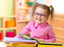 Jong geitje in oogglazen of bril die boeken in haar ruimte lezen royalty-vrije stock foto