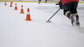 Jong geitje opleiding hockey en behandelingspuck met hindernissen tussen wegkegels op het ijs binnen piste stock footage