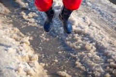 Jong geitje in rainboots die in de ijsvulklei springen Stock Afbeeldingen
