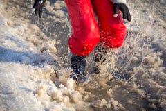 Jong geitje in rainboots die in de ijsvulklei springen Royalty-vrije Stock Afbeeldingen