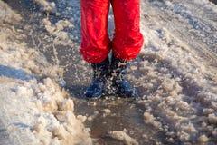 Jong geitje in rainboots die in de ijsvulklei springen Stock Fotografie
