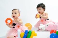 Jong geitje in roze kleding het spelen stuk speelgoed stock afbeeldingen