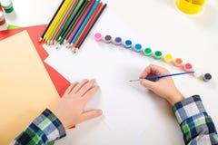 Jong geitje` s tekening Kunstachtergrond met kleurrijke potloden, verven en leeg document Jong geitjehanden met borstel op een do stock afbeelding