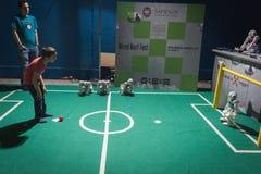 Jong geitje speelvoetbal met Nao robot in Getelegrafeerde Volgende Fest in Milaan, Italië Royalty-vrije Stock Afbeeldingen