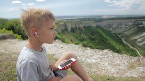 Jong geitjejongen die aan muziek met hoofdtelefoons op smartphone op een achtergrond van bergen luisteren stock video