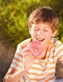 Jong geitjejongen die doughnut in openlucht eten stock afbeelding