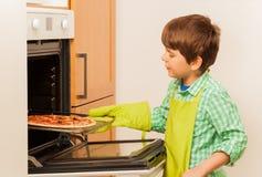 Jong geitjejongen die eigengemaakte pizza in de oven zetten royalty-vrije stock afbeeldingen