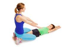 Jong geitjejongen die gymnastiek met vrouwelijke trainer maken Royalty-vrije Stock Afbeelding