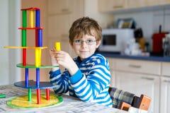 Jong geitjejongen die met glazen met veel kleurrijk houten blokkenspel spelen binnen Stock Afbeelding