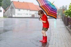 Jong geitjejongen die rode regenlaarzen dragen en met paraplu lopen royalty-vrije stock afbeeldingen