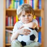 Jong geitjejongen het letten op voetbal of voetbalspel op TV Stock Afbeelding