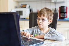 Jong geitjejongen met glazen die Internet surfen en op computer spelen royalty-vrije stock foto