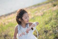 jong geitjemanier Leuk weinig Aziatisch meisje die wit kleren en bloemgras in haar hand dragen stock afbeelding
