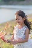 jong geitjemanier Leuk weinig Aziatisch meisje die wit kleren en bloemgras in haar hand dragen royalty-vrije stock afbeeldingen