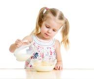 Jong geitjemeisje die cornflakes met melk voorbereiden Stock Afbeelding