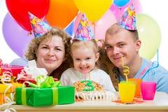 Jong geitjemeisje met ouders op verjaardag royalty-vrije stock afbeelding