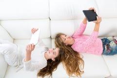 Jong geitjemeisjes die pret het spelen met het liggen van tabletpc bank hebben royalty-vrije stock afbeeldingen