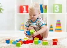 Jong geitjepeuter die houten speelgoed thuis of kinderdagverblijf spelen stock afbeelding