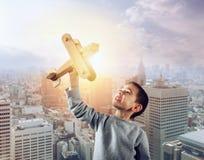 Jong geitjespelen met een houten stuk speelgoed vliegtuig stock fotografie
