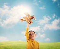 Jong geitjespelen met een houten stuk speelgoed vliegtuig stock afbeeldingen