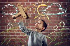 Jong geitjespelen met een houten stuk speelgoed vliegtuig stock foto