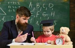 Jong geitjestudies met leraar, die met aandacht luisteren Elementair onderwijsconcept De vader onderwijst elementaire zoon royalty-vrije stock afbeeldingen
