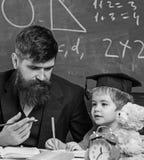Jong geitjestudies met leraar, die met aandacht luisteren Elementair onderwijsconcept Leraar en leerling in baret royalty-vrije stock foto