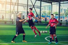 Jong geitjevoetbal opleiding met sprong voor slag aan bal ter beschikking van bus stock foto