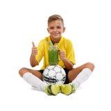 Jong geitjezitting met bal en smoothie geïsoleerd op een witte achtergrond Actieve schooljongen die een duim tonen Het concept va Stock Afbeeldingen