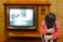 Jong geitjezitting met droefheid en zieken van TV-de liefde van de verslaafdenbehoefte van Royalty-vrije Stock Foto's