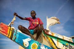 Jong geitjezitting op een gekleurde vissersboot in Senegal stock foto