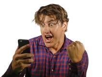 Jong gek gelukkig en opgewekt mens het vieren succes die geld maken het online gokken met mobiele telefoon die Internet-ge?soleer stock afbeelding